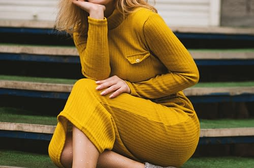 woman in yellow dress, grey boots and yellow sunglasses