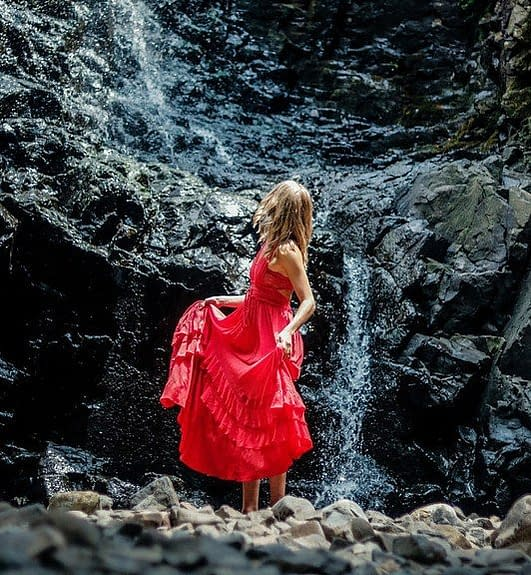 a woman dressed in a red dress in front of a small waterfall coming down a graphit grey wall