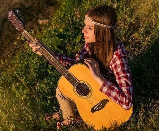 A hippy woman sitting in the grass playing guitar
