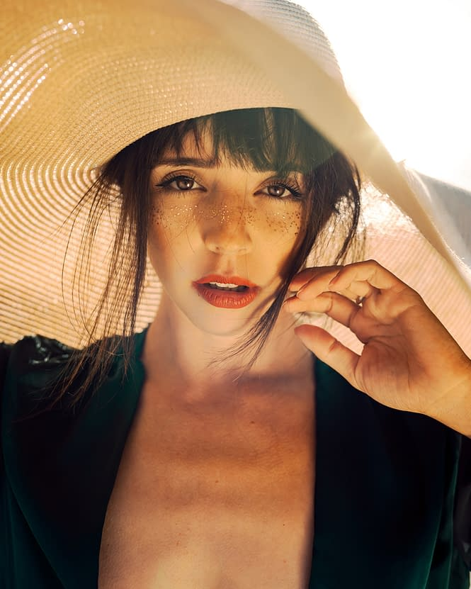 Beautiful woman in green dress with a straw hat covering her dark hair