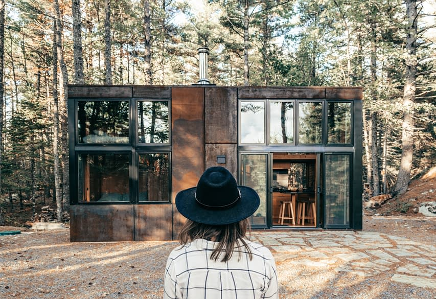 tiny house in the forest, woman with black hat sitting in front of the house