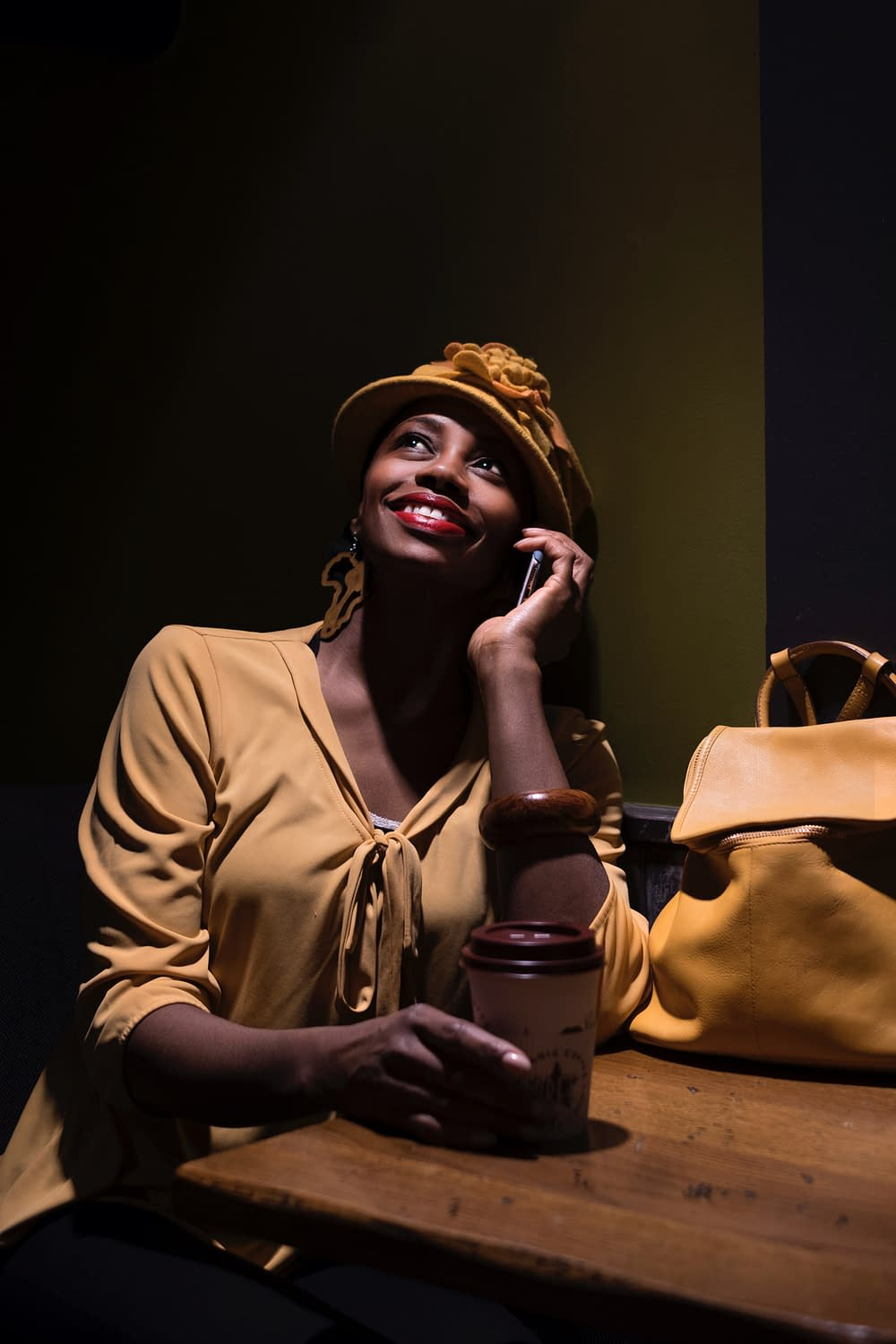 woman in yellow,handbag,hat, sitting in a coffee shop,smiling