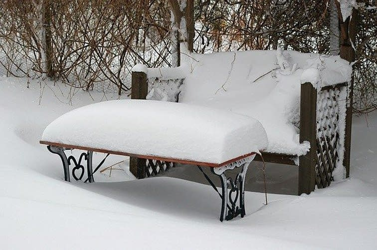 bench and table snow covered in a garden