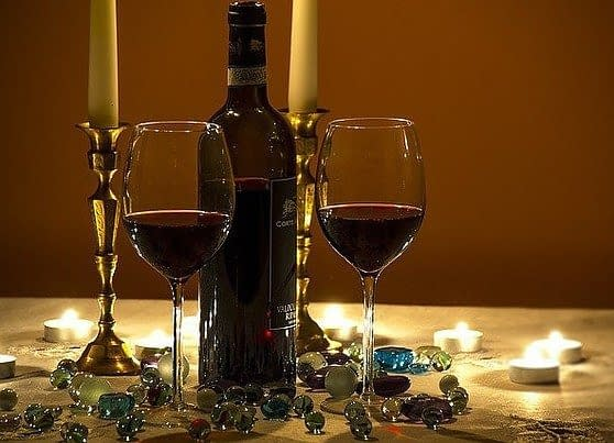 two candles,a bottle of redwine and two filled wine glasses on a table, covered with blue cristals