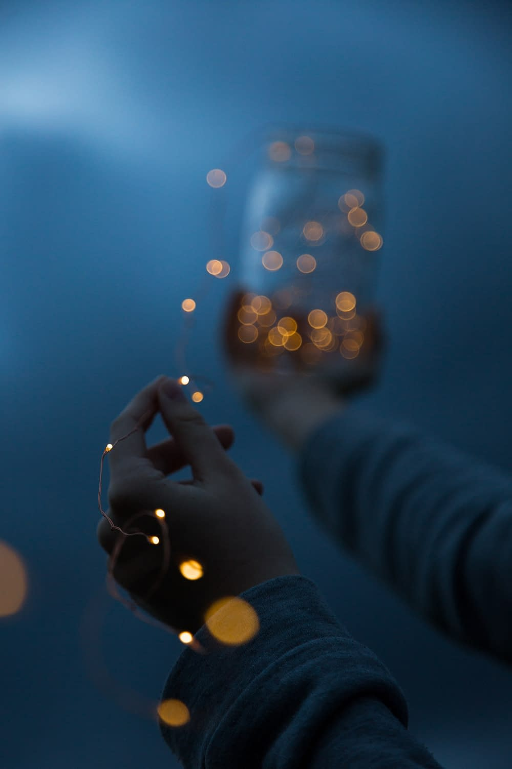 woman holding a yellow string light and a glass