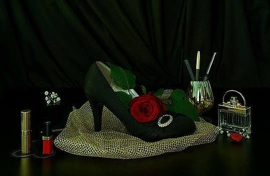 green elegant shoe with a red rose, and a pearl broche, makeup pencils, lipstick, flacon with perfume on a golden colored material