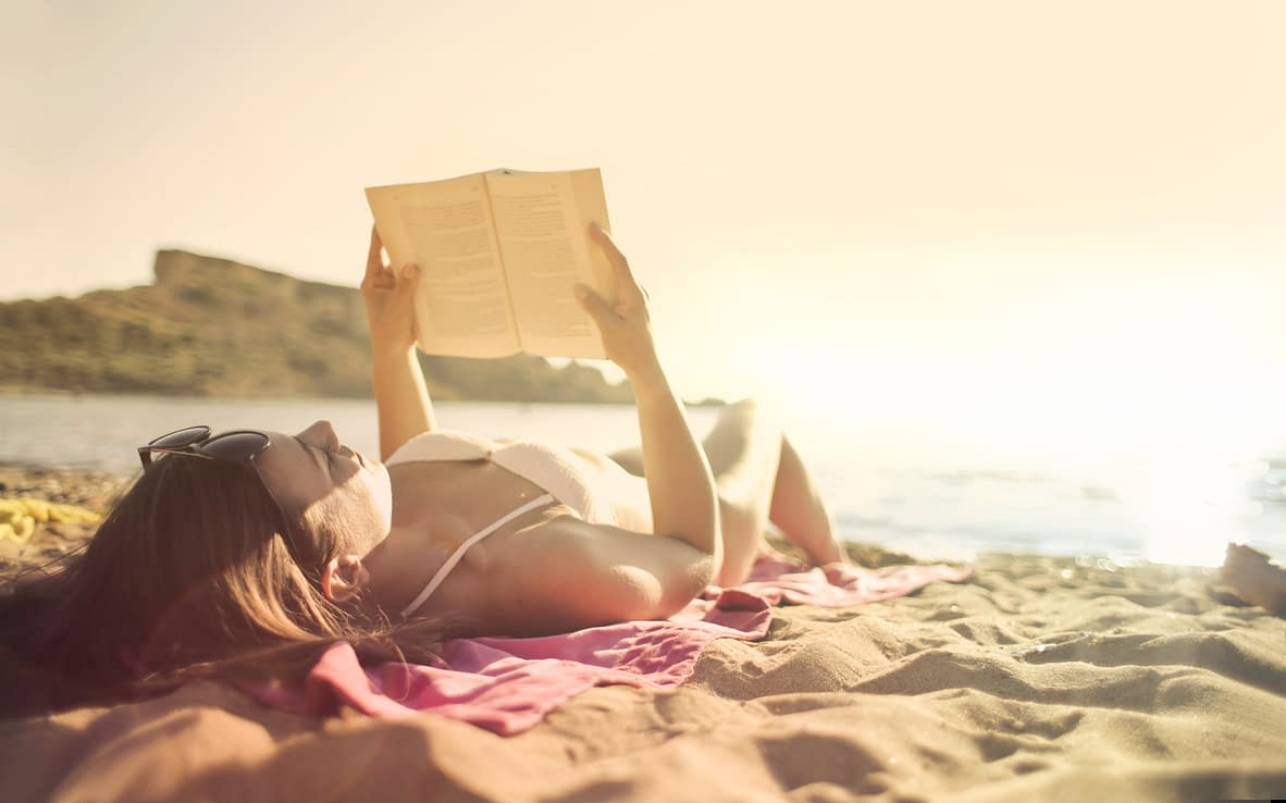 a woman reading a book lying at the beach