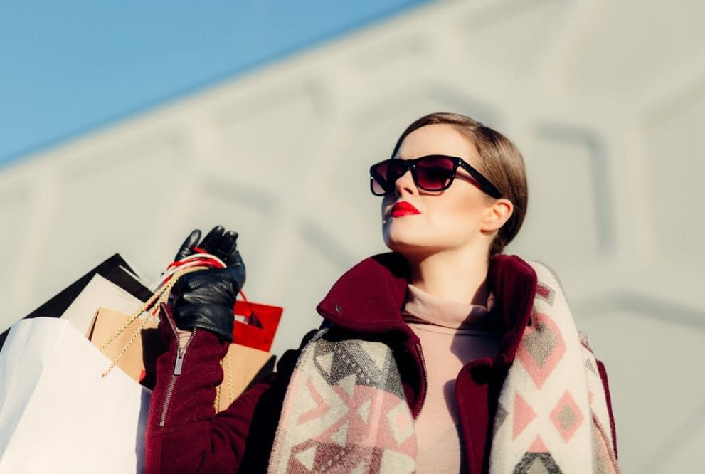 woman with sunglasses wearing luxary clothing, hand gloves and bags