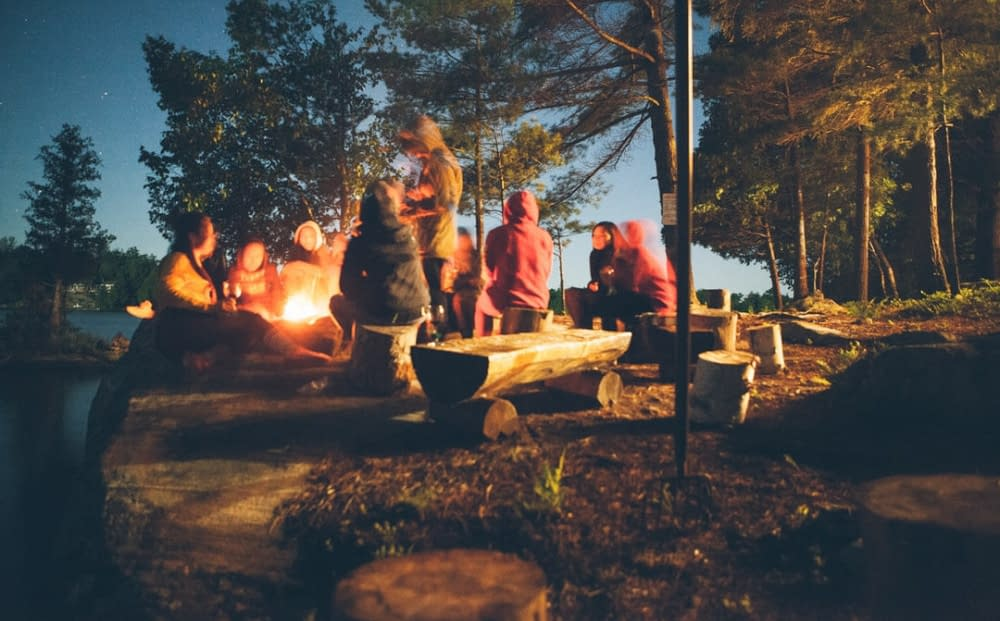 a group of people around a fire, camping