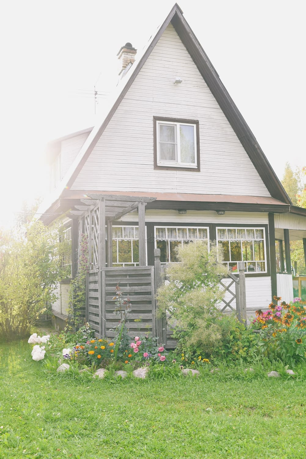 white tiny house, surrounded by a garden