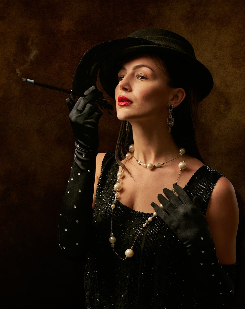woman in black dreaa and black gloves, black hat, with pearls and earings