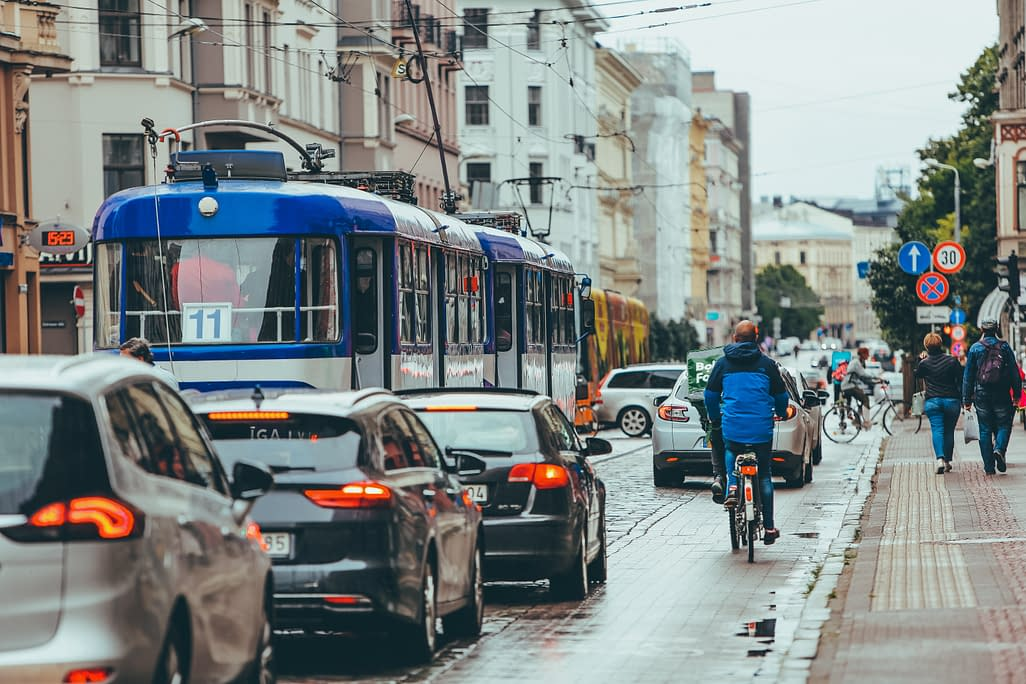 a man cycling near car an d a tram