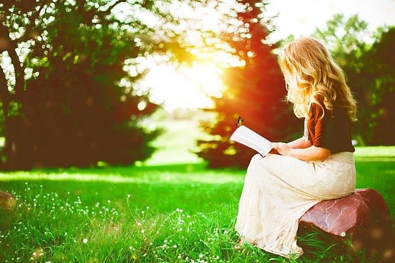 a woman sitting and reading in a park by sunshine