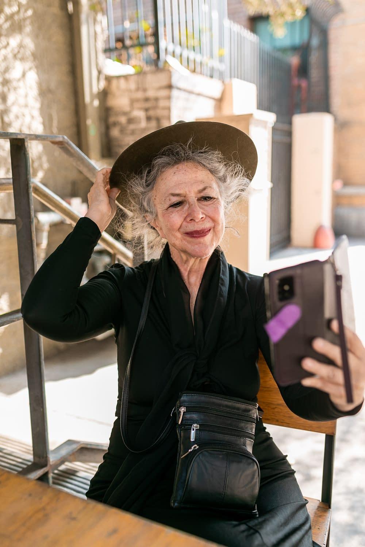 elderly woman with hat taking a selfie