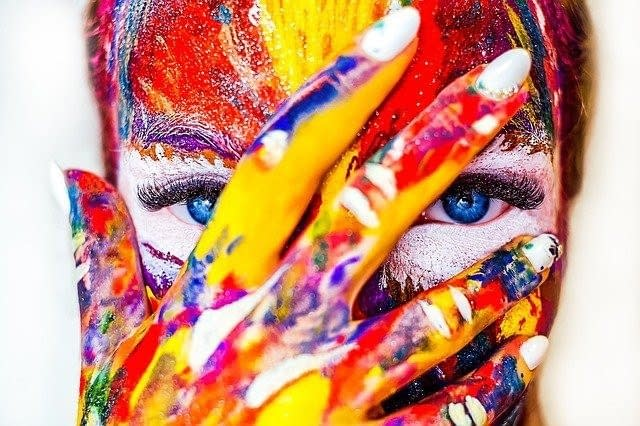 A colored in all different colors face covered by a hand