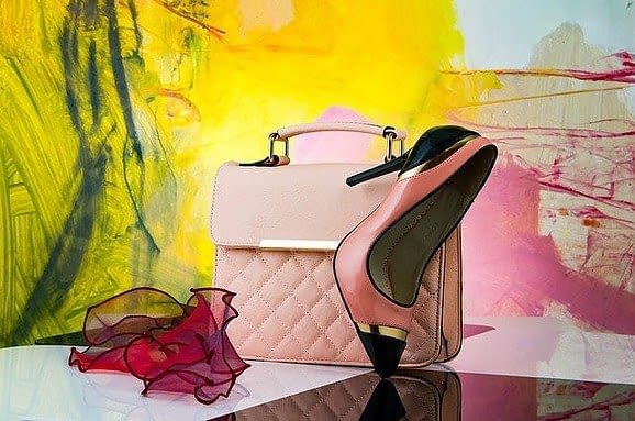 A pink colored high heel shoe, a handbag and a scarf on a table
