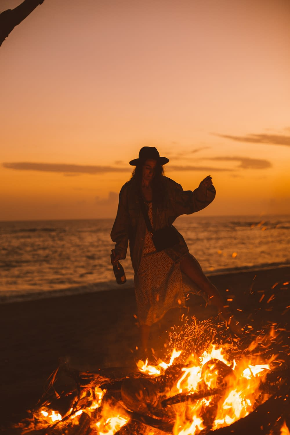 a woman dancing around a fire at the beach