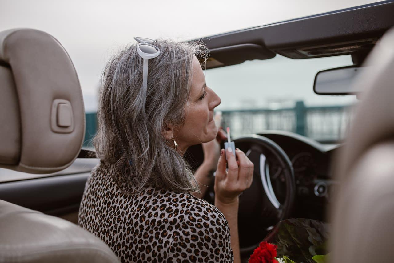 stylish woman in her Cabrio, using lipstick