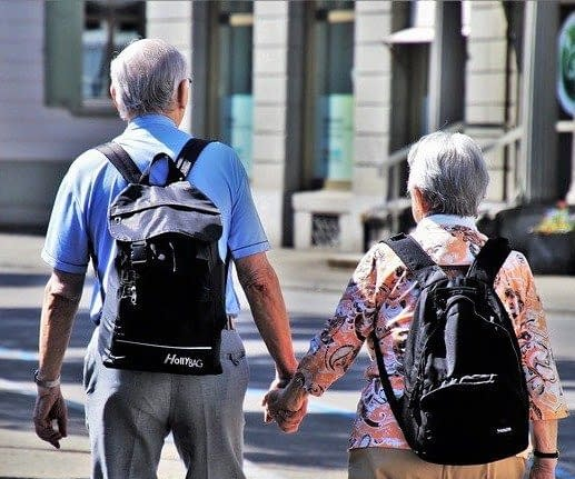 a old couple travelling hand in hand in a city