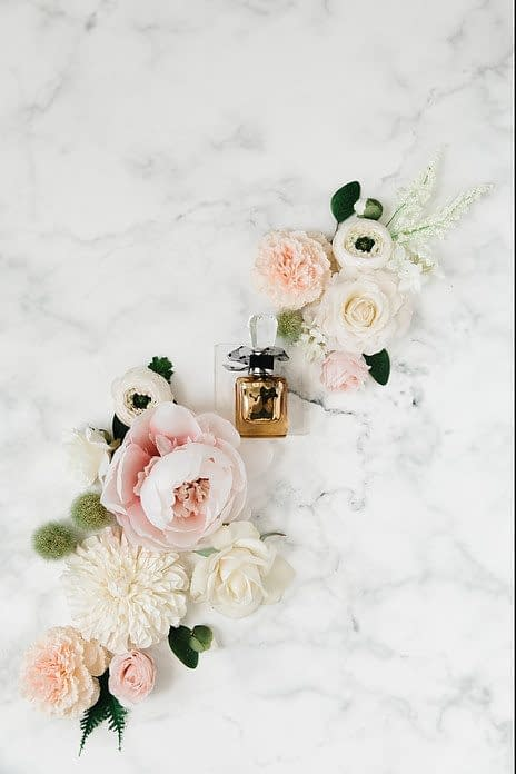 a bottle of perfume between roses