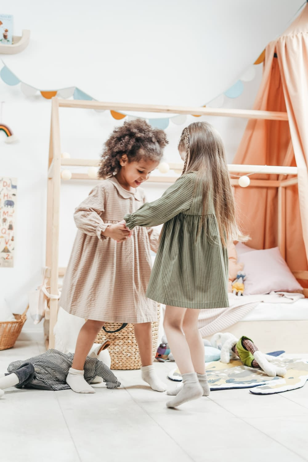 2 small girls dancing on a bed, holding each other hands