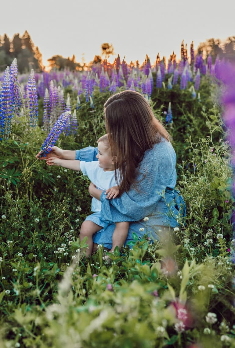 a mother with her baby sitting in a field of wild flowers