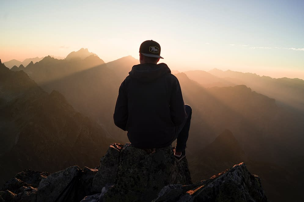 a young man sitting high up in the mountains at sun set
