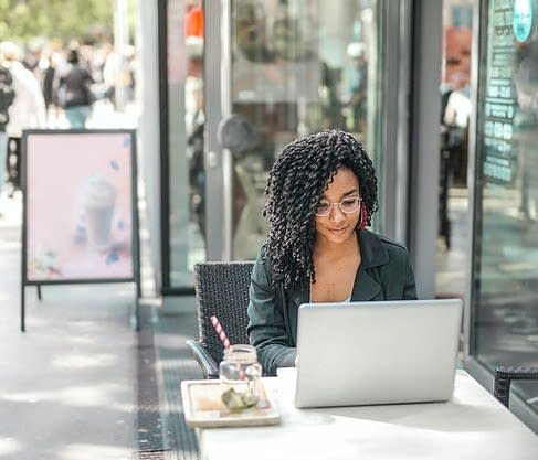 woman with curly hair sitting with her laptop in a cafe outside at a table, working.